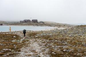 Snøheim dukker opp over siste bakkektopp. Lave skyer / tåke denne dagen, etter overnatting inne i Storstyggsvånådalen.